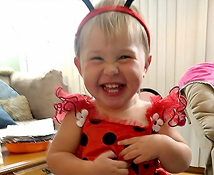 little girl dressed like a ladybug laughing at camera