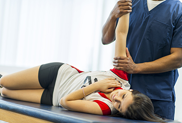 Teen athlete receiving physical therapy on her shoulder