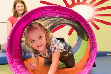 child crawling through colorful tunnel in developmental therapy