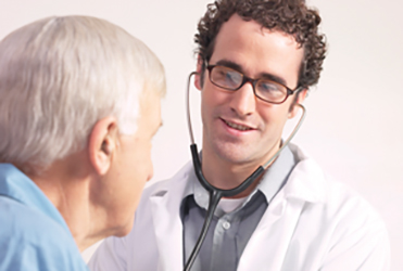 Doctor with stethoscope talking to senior male patient