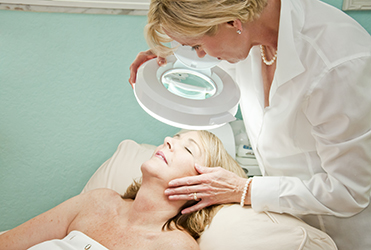 Middle age woman's skin being examined