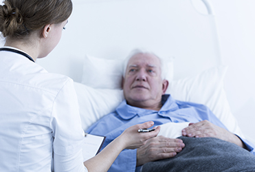 Doctor talking to man in hospital bed