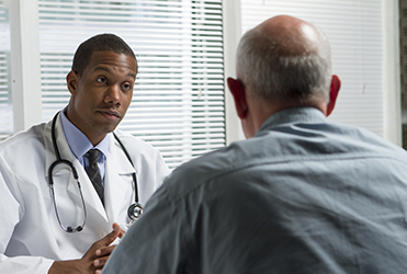 man speaking to his SSM Health physician across a desk
