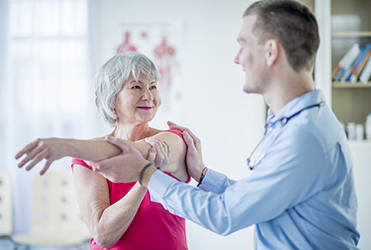 Woman receiving physical therapy on her shoulder