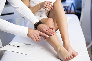 Woman's leg bring examined by doctor