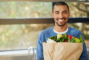 Young man holding bag of healthy groceries