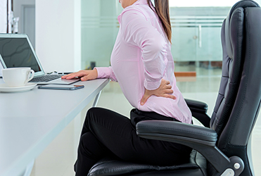 Woman in desk chair clutching back