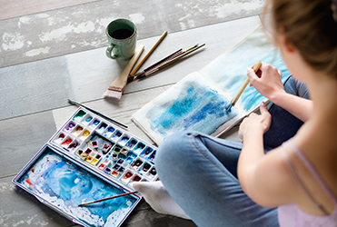 young woman painting with water colors